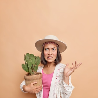 Irritated asian lady bites lips raises palm looks angrily above holds potted cactus wears fedora white knitted coat poses against brown wall copy space for your promotion