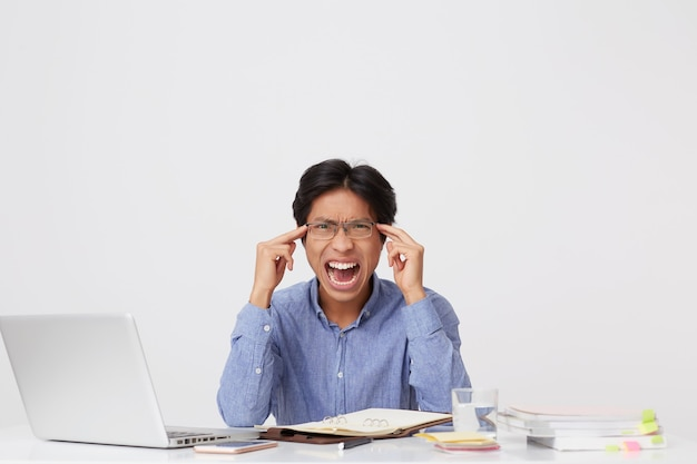 Irritated asian young business man in glasses with mouth opened touching temples and shouting sitting at the table over white wall