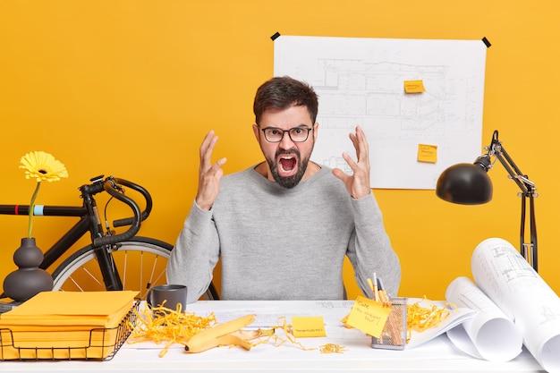 Imprenditore o architetto barbuto irritato si sente molto arrabbiato esclama ad alta voce ha molto lavoro da fare posa su un desktop disordinato indossa occhiali lavora al progetto di avvio esprime emozioni negative