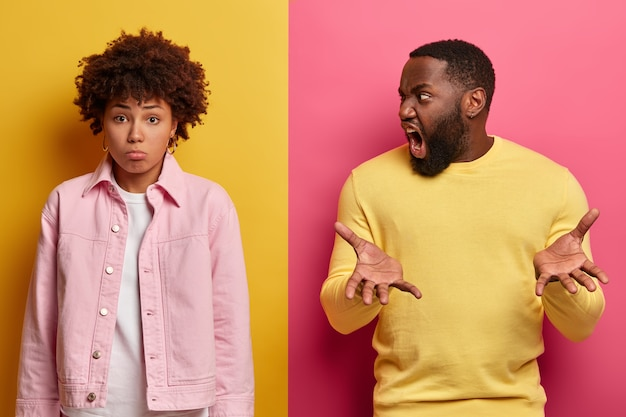 L'uomo barbuto irritato grida con rabbia alla ragazza, incolpa di aver fatto qualcosa di sbagliato, alza i palmi
