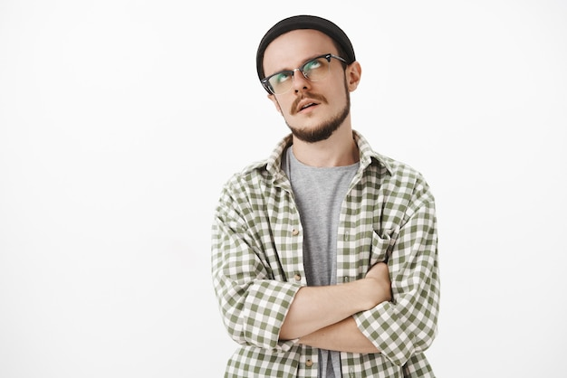 Irritated bothered and annoyed young caucasian guy with beard in transparent glasses and beanie rolling eyes up and crossing hands on chest being dissatisfied