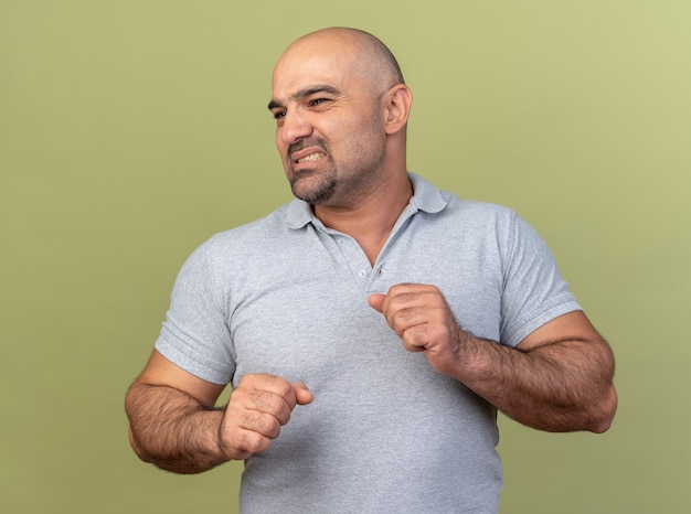 Irritated casual middle-aged man looking at side clenching fists isolated on olive green wall