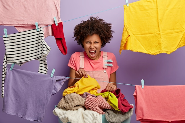 Irritated curly haired housewife screams with annoyance, picks up dirty linen with unpleasant stench, busy doing washing at home during weekend, surroundeed by hanged wet clean clothes on rope