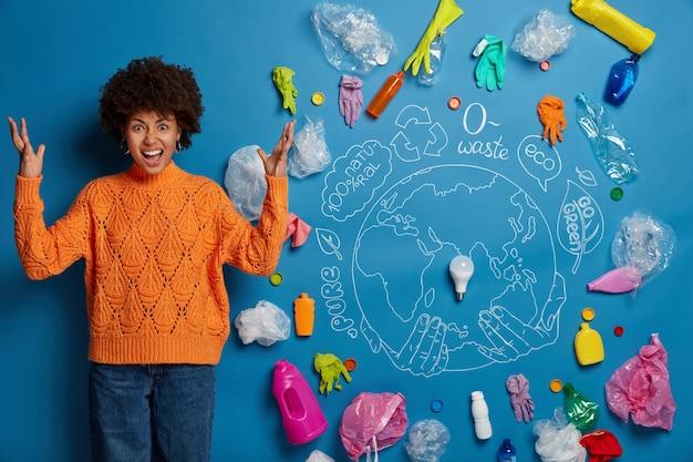 イライラした縮れ毛の女性は、大きな環境問題、プラスチック廃棄物に対するジェスチャー、汚染者に悩まされていることを懸念して、怒りで両手を上げます。