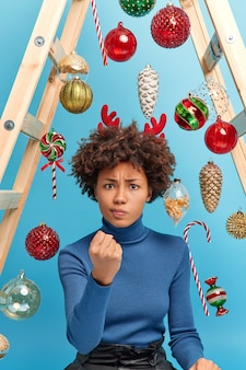 Irritated curly woman clenches fist and looks annoyed being angry with naughty children who help decorate house for new year enjoys day off at home poses