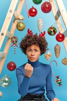 La donna riccia irritata stringe il pugno e sembra infastidita dall'essere arrabbiata con i bambini cattivi che aiutano a decorare la casa per il nuovo anno si gode le pose del giorno libero a casa