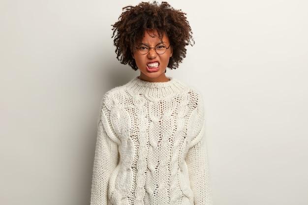 Раздраженная темнокожая женщина ухмыляется, у нее раздраженный вид, хмурится нос и стиснет зубы, у нее вьющиеся волосы, она одета в длинную зимнюю одежду, изолирована за белой стеной, чувствует стресс и злится.