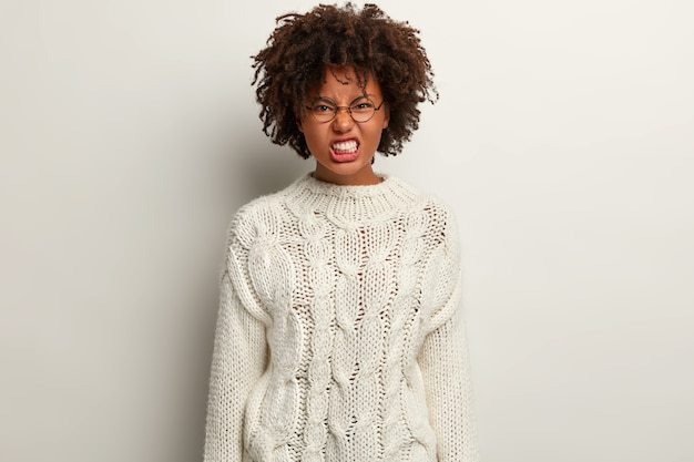 Irritated dark skinned female smirks face, has annoyed look, frowns nose and clenches teeth, has curly hair, dressed in long winter clothes, isolated over white wall, feels stress and mad