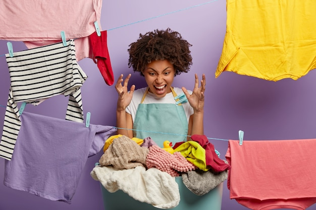 Irritated dark skinned woman raises arms, looks angirly at pile of dirty linen, doesnt want to wash clothes by hands as washing machine is broken, hates laundry process, wears apron with clothespins
