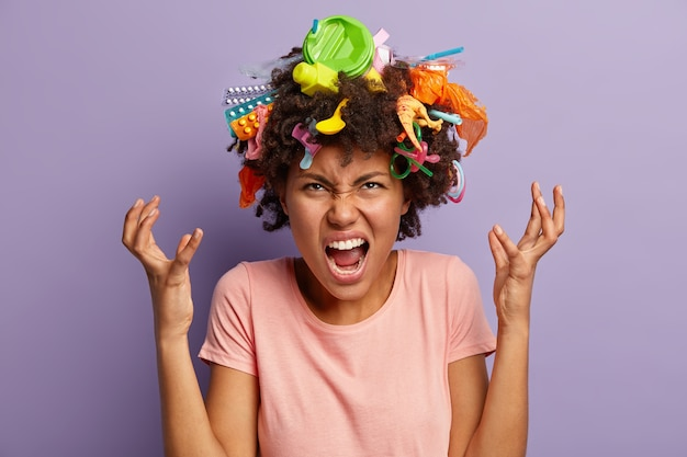 Irritated dark skinned woman screams angrily, raises hands, demonstrates garbage she collected on hair, annoyed with irresponsible people who throw rubbish everywhere. environmental damage concept