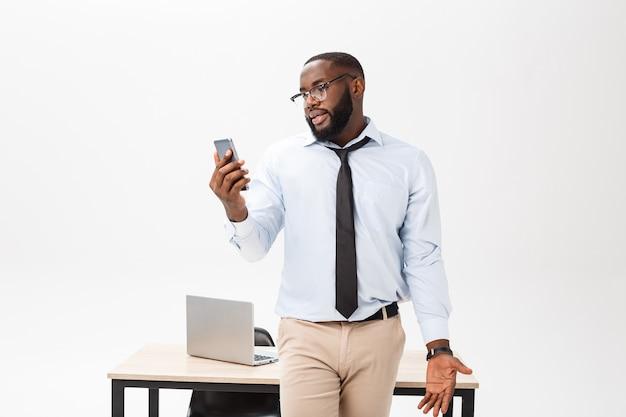職場にいるイライラした暗い肌の若い男性のエンタープレナーは非常にストレスと怒りを感じます