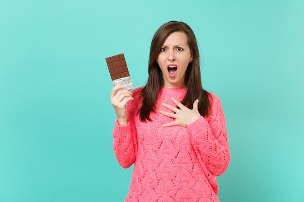 Раздраженная отвращение молодая женщина в вязаном розовом свитере держит плитку шоколада, положила руку на грудь, изолированную на синем фоне бирюзовой стены. студийный портрет. концепция образа жизни людей. копируйте пространство для копирования.