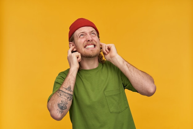 Irritated, displeased bearded guy with blond hair. wearing green t-shirt and red beanie. has tattoos. closes his ears, annoyed from noise. watching up at copy space, isolated over yellow wall