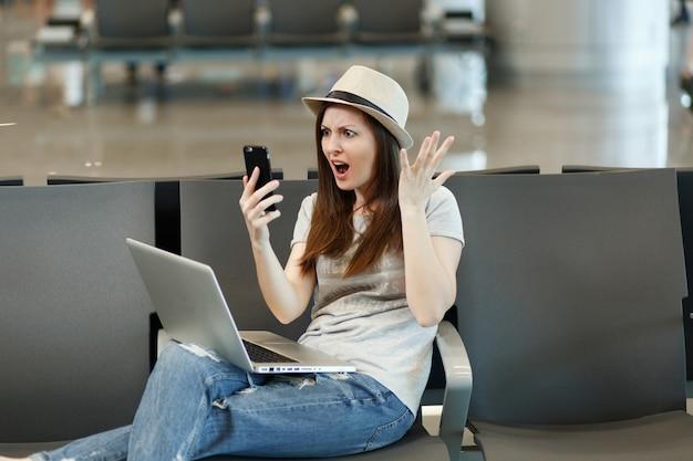 노트북 보류 휴대 전화와 짜증이 불만족 여행자 관광 여자 국제 공항 로비 홀에서 손을 기다립니다