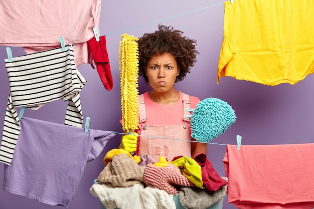 Irritated dissatisfied woman has afro haircut, holds washing tools, stands near ropes with hanged clean clothes for drying, busy with housework, angry with daily chores about house. household concept