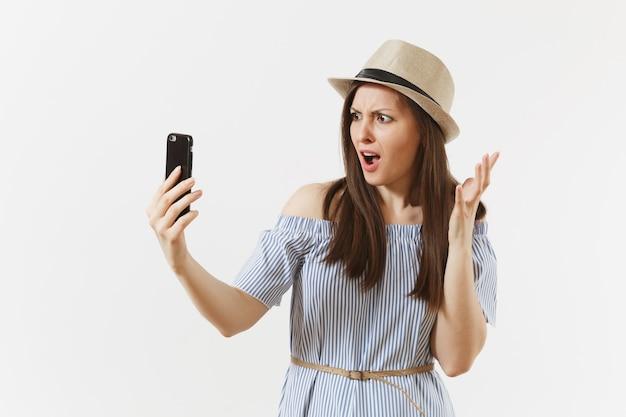 파란 드레스를 입은 불만스러운 여성, 휴대전화로 셀카 촬영을 하는 모자, 흰색 배경에 격리된 화상 통화. 사람, 진실한 감정, 라이프 스타일 개념. 광고 영역입니다. 공간을 복사합니다.