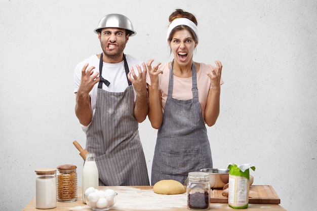 Irritated female and male cooks, keep hands in furious gesture, being annoyed with chef