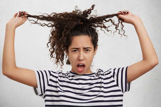 Il modello femminile irritato tiene le mani sulle ciocche ricci, vuole avere i capelli lisci, sembra dispiaciuto