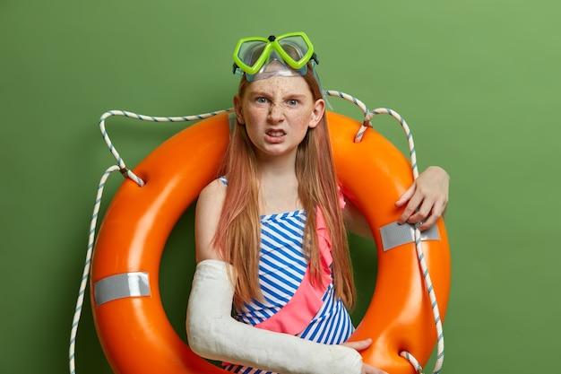 イライラした女の子は、腕が折れたために泳げず、キャストを着用し、水泳用ゴーグルと膨らんだリングでポーズをとり、夏休みを楽しみ、海の近くで再現し、緑の壁に向かってポーズをとります。子供たち、休む