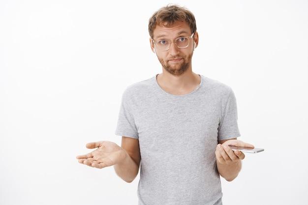 スマートフォンを保持しているワイヤレスイヤホンで無知なジェスチャーで歌を聞いて広げた手で肩をすくめて眼鏡をかけたイライラしたハンサムな男