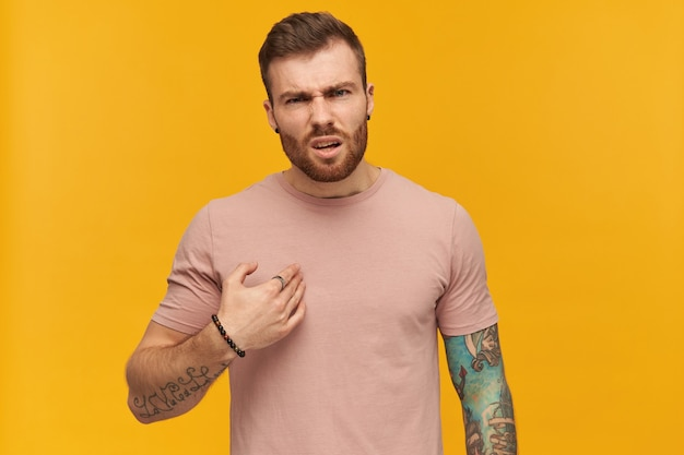 Irritated handsome young man in pink tshirt with beard and tattoo on hand points at himself by hand and looks annoyed over yellow wall