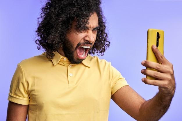 보라색 벽에 고립 된 휴대 전화, 비명, 온라인으로 이야기하는 동안 스마트 폰에서 외치는 자극 된 남성