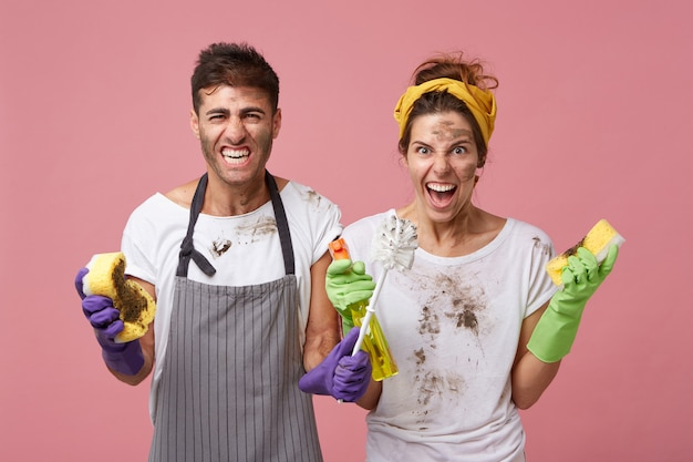 Irritated male and woman from cleaning service wearing dirty clothes holding cleaning equipment frowning their faces being busy with cleaning looking at untidy furniture with disgust and anger