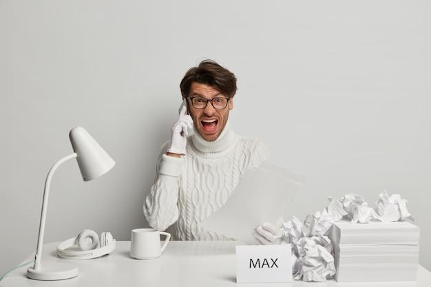 イライラした男性労働者が電話で会話し、同僚に怒鳴り、イライラする仕事