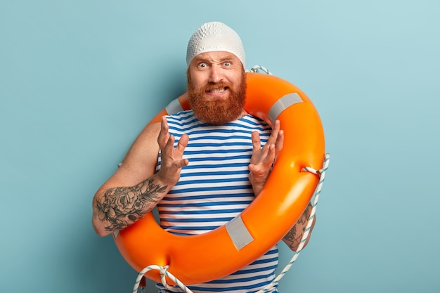 Irritated man with red thick beard, gestures with annoyance, wears rubber swimcap