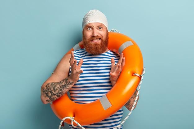 赤く厚いあごひげを生やしたイライラした男、迷惑なジェスチャー、ゴム製のスイムキャップを着用