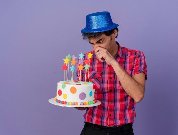 Uomo caucasico irritato del partito di mezza età che indossa il cappello del partito che tiene e che guarda la torta di compleanno che tocca il naso isolato su fondo viola con lo spazio della copia