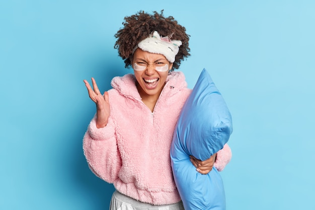 イライラしたミレニアル世代の女の子が手を挙げて、パジャマで睡眠ポーズを中断する騒々しい隣人に腹を立てて怒って叫ぶ青い壁に隔離された柔らかい枕を保持します