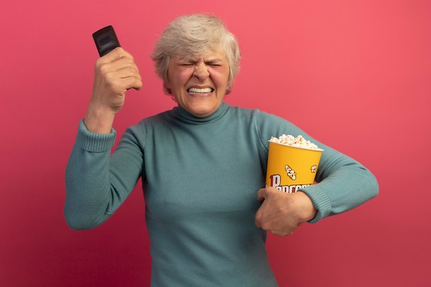 Vecchia donna irritata che indossa un maglione blu a collo alto che tiene il secchio di popcorn e il telecomando vicino alla testa con gli occhi chiusi