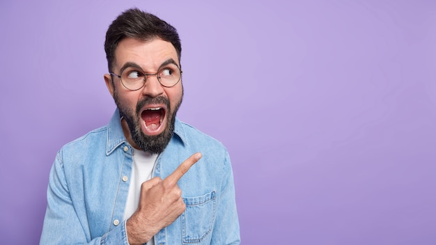 Irritated outraged bearded man screams loudly opens mouth points at upper right corner being annoyed by very high prices in store wears round spectacles denim shirt