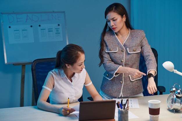 Раздраженный руководитель проекта указывает на наручные часы, когда просит дизайнера доработать интерфейс мобильного приложения за ночь до крайнего срока
