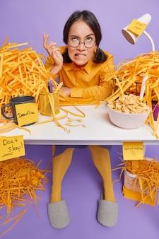 Studentessa perplessa irritata che morde le labbra ha molto lavoro da fare siede da sola al desktop ha una scadenza per prepararsi per il test ha cereali per colazione circondata da fogli tagliati isolati sul muro viola