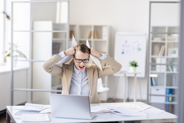 Irritated puzzled young business lady in glasses sitting at table and holding head in hands with papers while knowing about failure of her project