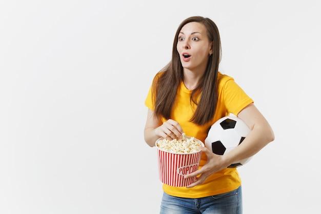 イライラしてショックを受けたヨーロッパの女性、サッカーボールを保持している黄色の制服を着たサッカーファン、白い背景で隔離のポップコーンのバケツ。スポーツ、サッカー、応援、ファンの人々のライフスタイルのコンセプト。