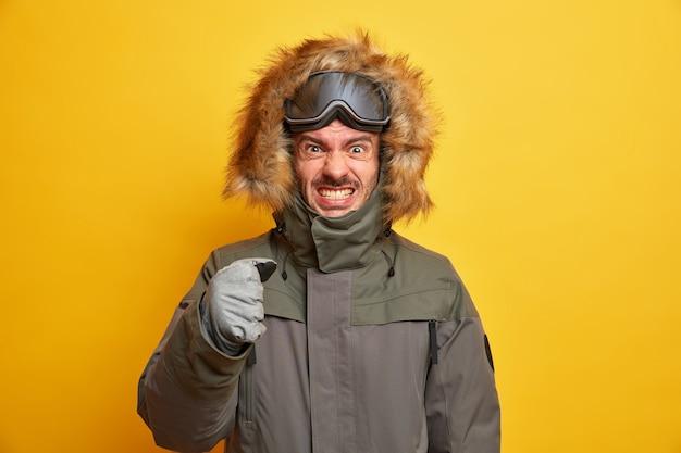 Snowboarder irritato stringe i denti dalla rabbia trascorre le vacanze invernali in montagna stringe il pugno indossa giacca e guanti dispiaciuto per il freddo.