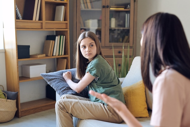 Irritated teenage daughter listening to mother who scolding her at home