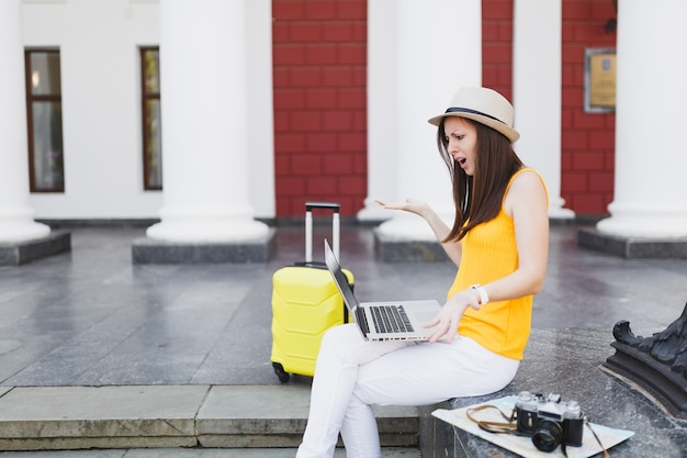 Irritated traveler tourist woman with suitcase sit on stairs using working on laptop pc computer spreading hands outdoor. girl traveling abroad to travel on weekend getaway. tourism journey lifestyle.