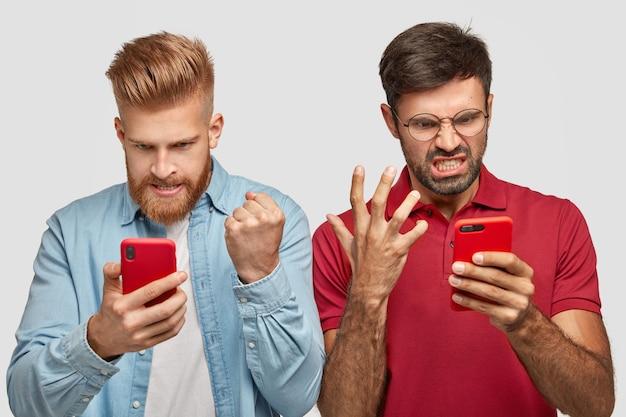 Раздраженные два парня сердито смотрят на экран смартфона, смотрят футбольный матч онлайн, раздраженные проигрышем любимой командой игры, сосредоточены на чем-то, одеты в модную одежду, позируют в помещении