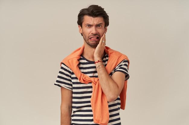 줄무늬 티셔츠에 강모와 어깨에 스웨터가있는 짜증을 낸 불행한 청년은 손을 뺨에 유지하고 짜증을 느낍니다.