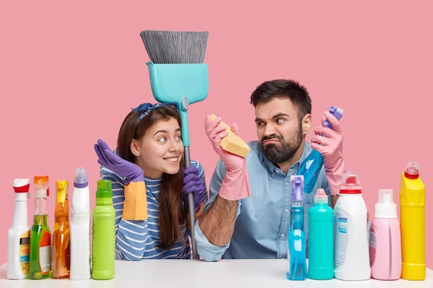 Irritated unshaven man frowns face, looks with dissatisfaction on cheerful wife, use cleaning supplies, pose at desktop with detergents