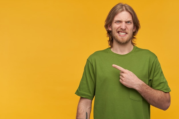 Irritated, unsure guy with blond hair, beard. wearing green t-shirt. has tattoo. wry his face.  and pointing finger to the left at copy space, isolated over yellow wall