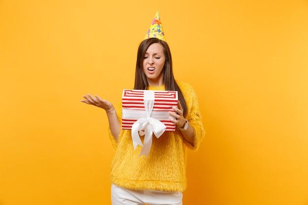 明るい黄色の背景に分離されたプレゼント、贈り物と赤い箱を持って手を広げて誕生日パーティー帽子でイライラして動揺している若い女性。人々の誠実な感情、ライフスタイルのコンセプト。広告エリア。