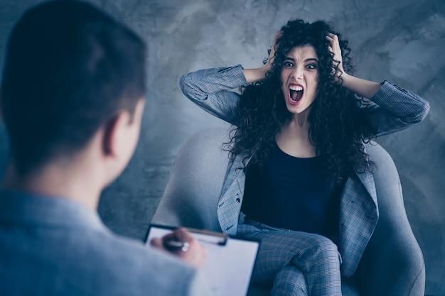 Раздраженная девушка с волнистыми волосами сидит в кресле и кричит психиатру на фоне бетонной стены