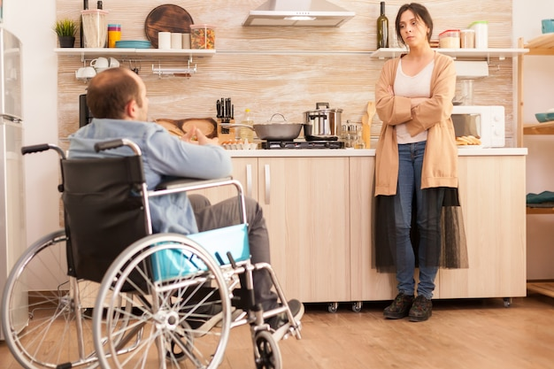 Irritated wife in kitchen because of disagreement with disabled husband in wheelchair. disabled paralyzed handicapped man with walking disability integrating after an accident.