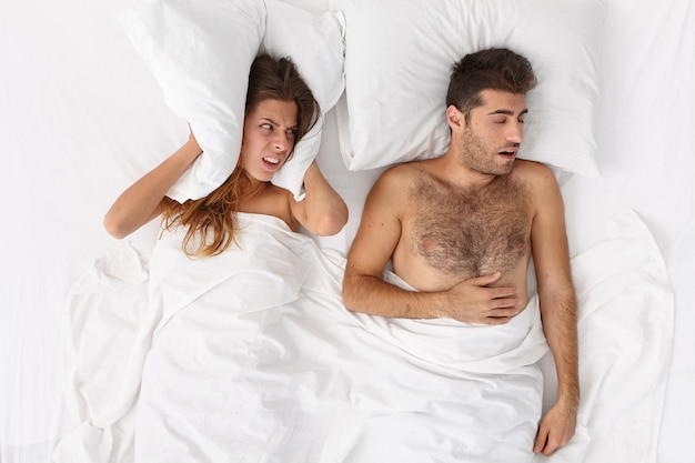 Irritated woman blocks ears, covers by pillow, looks with anger at snoring husband, cannot fall asleep, feels annoyed, has problems with sleeping, lie in white bed. man has problems of sleep apnea