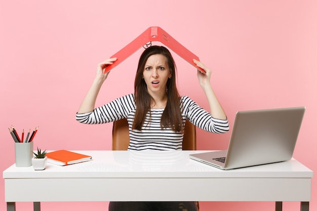 Irritated woman holding red folder with paper document above head like roof working on project while sitting at office with laptop isolated on pink background. achievement business career. copy space.